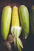 Four corncobs on a wooden background