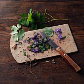 Columbine, chopped on a wooden board (for making columbine honey à la Hildegard von Bingen)