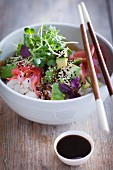 A sushi bowl with avocado, cress, soy sauce and pickled ginger