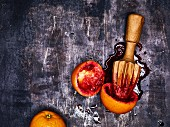 Juiced blood oranges with a wooden citrus juicer on a metal surface