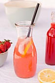 A carafe of homemade rhubarb and strawberry lemonade with lemons