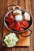 Grilled chicken wings and legs with baked potatoes, tzatziki and cucumber coleslaw