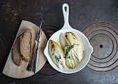 Oven-baked chicory with Roquefort with Thai green pepper and country bread on a wooden board
