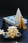 A pile of gluten-free Christmas biscuits with paper Christmas trees