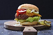A hamburger on a wooden board