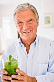 An older man holding a glass of green smoothie