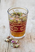 Black tea with dried rose petals in an oriental tea glass