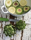 Artichokes ready to cook in a pot with a knife next to it
