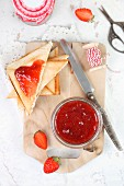 Homemade strawberry jam in a jar and on triangles of toast