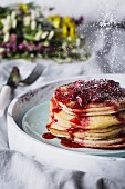 A stack of buttermilk pancakes with strawberry compote