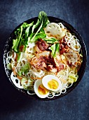 Egg noodle soup with pork belly, boiled egg, spinach, lotus roots and carrots (Asia)