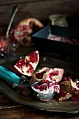 Fresh pomegranates and an ice cream scoop with pomegranate ice cream on a silver tray