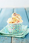 Vanilla ice cream with colourful sugar sprinkled in a paper tub