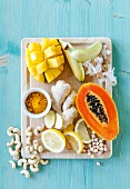 Yellow superfoods including mango, bananas, papaya, Ginger, turmeric, lemons and cashew nuts