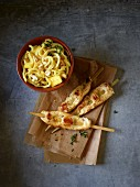 Chicken skewers and a celery spiral salad with pineapple, curry and cashew nuts