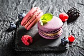 Macaroons with various berries on a black stone
