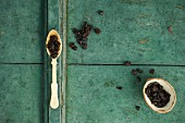 Dried cranberries on a spoon and in a bowl on a rustic surface