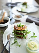 A potato burger with avocado and rocket on a plate