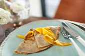Flambéed lemon and mango crepe on a plate