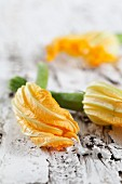 Courgette flowers on a white wooden surface