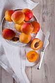 An arrangement of apricots with a halved apricot and an apricot stone
