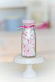 Pink and white peppermint hearts in a small glass bottle
