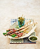 Pecorino breadsticks wrapped in ham with olives and pesto