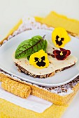 A slice of bread topped with chilli cheese, a bloodwort leaf and pansies