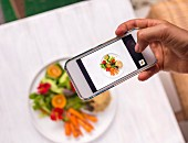Woman using a smart phone to take a photo of dish with quinoa and salad on a table