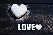 A heart-shaped doughnut and the word 'Love' in icing sugar on a wooden surface