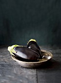 Two aubergines in a metal bowl with a knife