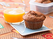 A chocolate muffin with honey served with a glass of orange juice
