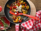 Colourful fried peppers and courgettes with sheep's cheese