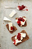 Slices of wholemeal bread topped with Camembert and cranberry jam