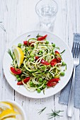 Courgette spaghetti with tomatoes and peas