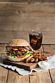 A beefburger with potato wedges, bacon, lettuce, cucumber, sour cream and a glass of cola