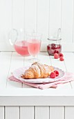 Breakfast with a croissant, raspberries, juice and raspberry jam