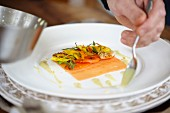Plating up smoked salmon with walnut, shallots and edible flowers