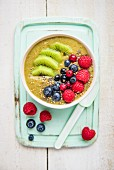 A smoothie bowl with matcha, kiwi and berries