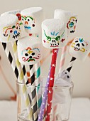 Marshmallows with spooky painted faces on straws