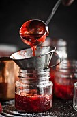 Strawberry jam being filled into a jar with a funnel