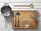 Assorted kitchen utensils: a sieve, a saucepan, cutlery, a small glass bowl and a measuring cup