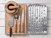Assorted kitchen utensils for barbecuing: a pestle and mortar, a grater, cutlery and a grill tray