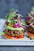 Mini burgers with bean patties, avocado cream, gherkin relish and cress