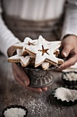 A woman holding a star shaped jam sandwich biscuits on a biscuit plate