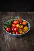 Various types of tomatoes in a bowl on a wooden surface