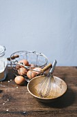 an arrangement of eggs in a wire basket and a wooden bowl with a whisk