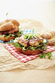 A Chinese chicken burger with cucumber and spring onions