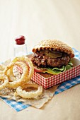 An all-American burger with gherkins and onion rings