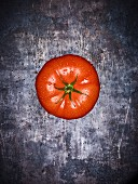 A beef tomato with droplets of water on a grey surface (seen from above)